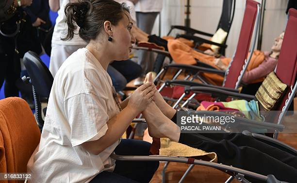 People receive a reflexology massage during the Salon de L'Humain on March 20 2016 in Toulouse southern France / AFP / PASCAL PAVANI
