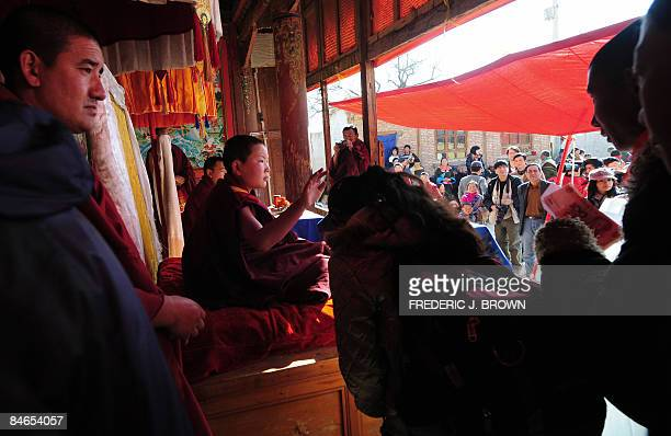 People receive blessings from Tibetan Buddhist monks at Gomar Gompa in Repkong during ongoing celebrations for Monlam or the Great Prayer Festival on...