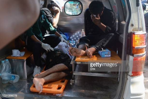 People receive first aid in the back of a vehicle after Myanmar police fired water cannon at protesters during a demonstration against the February 1...
