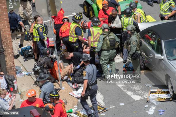 TOPSHOT People receive firstaid after a car accident ran into a crowd of protesters in Charlottesville VA on August 12 2017 A picturesque Virginia...