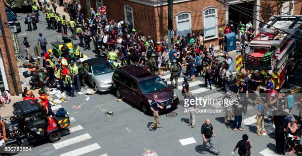People receive firstaid after a car accident ran into a crowd of protesters in Charlottesville VA on August 12 2017 A vehicle plowed into a crowd of...