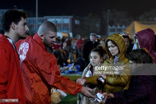 People receive food as they take shelter in a camp at the soccer stadium in Durres on November 26 after the strongest earthquake in decades claimed...