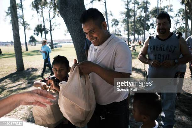 People receive food at the annual Thanksgiving in the Park gathering where residents of the farm worker community of Immokalee are provided with a...