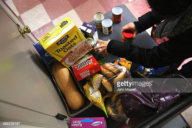 People receive free groceries at a food pantry run by the Food Bank For New York City on December 11 2013 in New York City The food bank distributes...