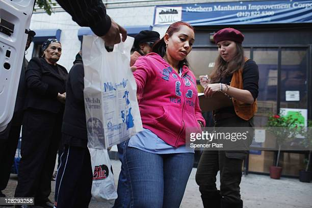 People receive free milk from the Milk from the Heart program which makes weekly deliveries to Washington Heights and 12 other locations in Manhattan...