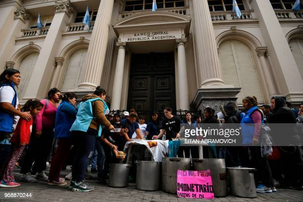 People receive meal from a soup kitchen outside Argentina's Central Bank in downtown Buenos Aires on May 15 2018 Argentina's currency faced a major...