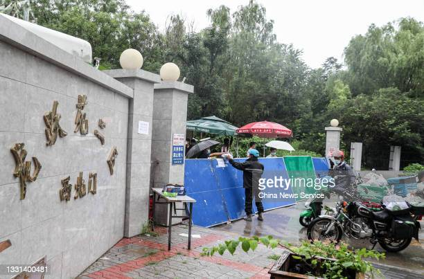 People receive supplies from deliverymen as the residential community is sealed off to prevent the COVID-19 spread on July 29, 2021 in Beijing, China.