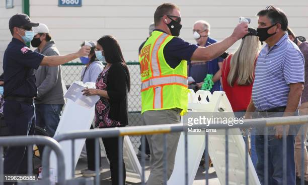 People receive temperature checks while waiting in line to receive the COVID-19 vaccine at a mass vaccination site in a parking lot for Disneyland...