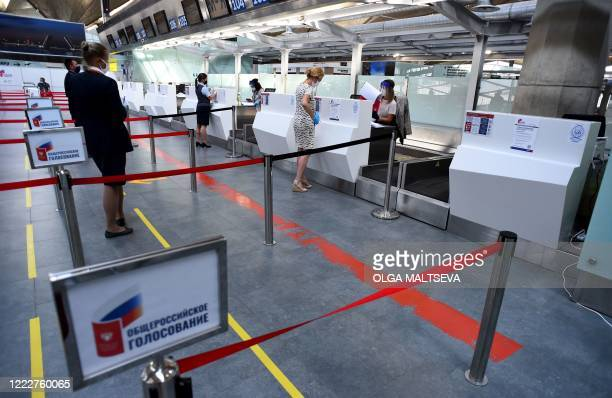 People receive their ballot papers during early voting on constitutional reforms at a polling station at Saint Petersburg's Pulkovo airport on June...