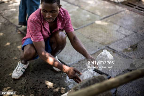 People refill water bottles at the Newlands spring tap one of many fresh mountain spring that runs through the city on February 14 2018 Citizens of...