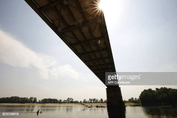 People refresh themselves in the Po River under the Ponte della Becca bridge in Linarolo near Pavia northern Italy on August 1 as the country is...