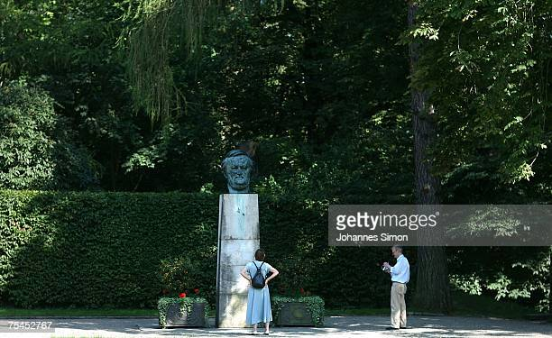 People regard the bronze head of German composer Richard Wagner designed by sculptor Arno Breker displayed in the park of Bayreuth festival hall on...