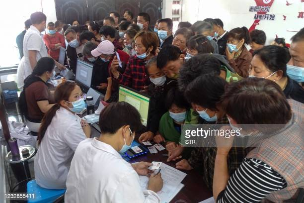People register information as they prepare to receive the Anhui Zhifei Longcom Covid-19 coronavirus vaccine in Linquan county, Fuyang city, in...