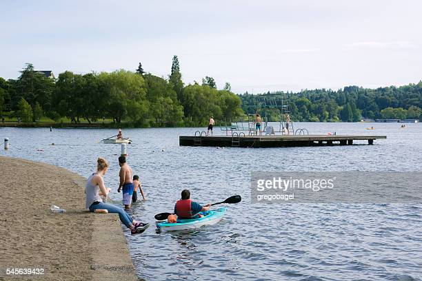 People relax along the shore at Green Lake in Seattle