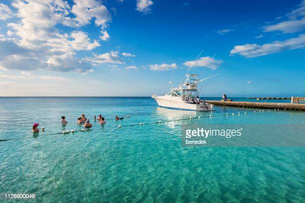 people relax and drink at doctor's cave beach in montego bay jamaica - montego bay stock pictures, royalty-free photos & images
