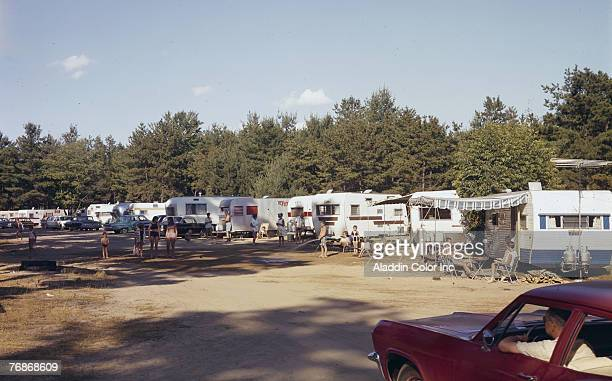 People relax and talk amid a row of parked campers and trailers at the Wagon Wheel Trailer Park Maine late 1950s or early 1960s Photo by Aladdin...