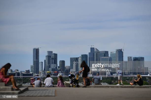 People relax as they take in the view of the London city skyline from Greenwich Park south east London on June 2 2020 following a further relaxation...