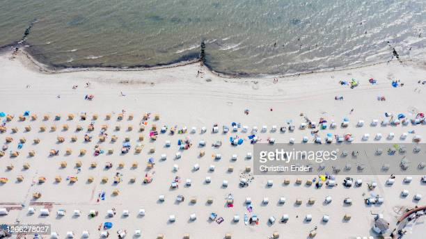 People relax at beach at high summer temperatures around 30 degrees Celsius during the novel coronavirus crisis on August 14, 2020 in Groemitz,...