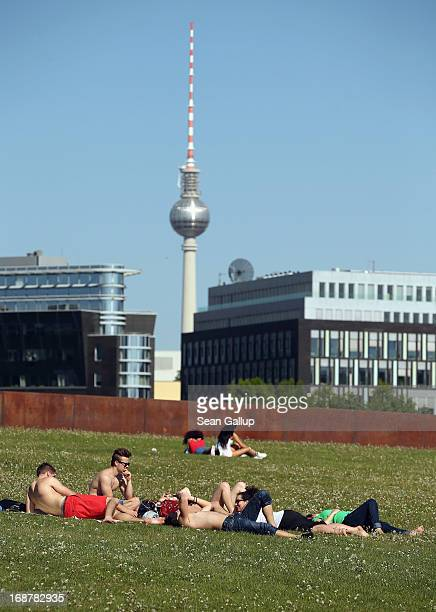 People relax in a park in the city center as the broadcast tower at Alexanderplatz looms behind on May 15 2013 in Berlin Germany Blue skies and warm...