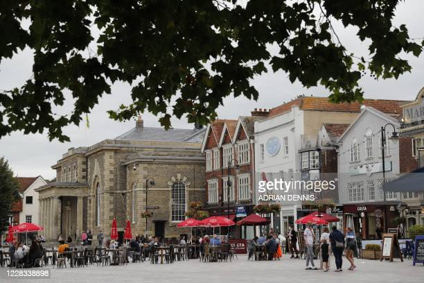 People relax in a square with outdoor seating near the Town Hall in Salisbury southern England on September 4 2020 A long way from the violent...