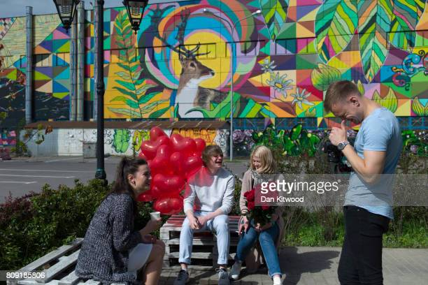 People relax in front of a piece of street art believed to be the largest mural in the world by Brazilian artist Ramon Martins on July 03 2017 in...