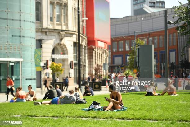 "People relax in he warm weather in the centre of Manchester, northwest England, on July 31, 2020. - Britain on Friday ""put the brakes on"" easing..."