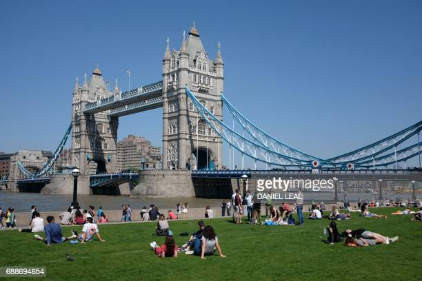People relax in the hot and sunny weather on the grass beside Tower Bridge and the river Thames in London on May 26 2017 Much of Britain enjoyed hot...