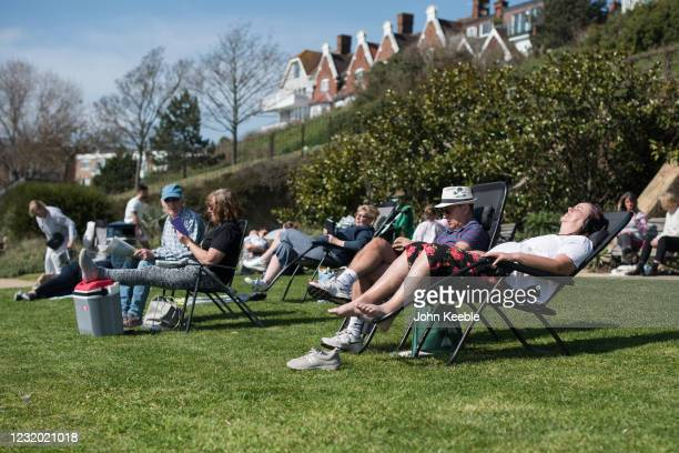 People relax in the sun on the green opposite the beach in Westcliff on March 30, 2021 in Southend, United Kingdom. Despite todays temperature...