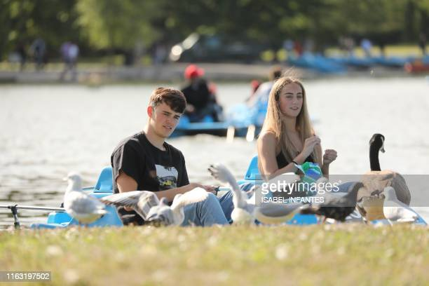 People relax in the sunshine by the boating lake in Regent's Park in London on August 22 2019