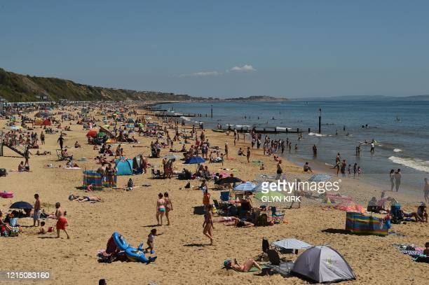 People relax in the sunshine on Boscombe Beach in Bournemouth, southern England on May 25 after lockdown restrictions put in place due the COVID-19...