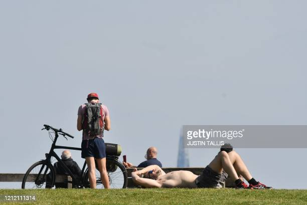 People relax in the sunshine on Primrose Hill in London on May 7 2020 as life continues in Britain under a nationwise lockdown to slow the spread of...