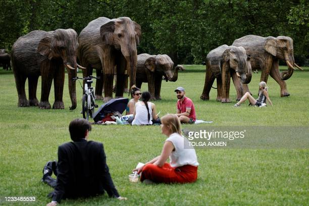 People relax near life-size sculptures of a herd of Asian elephants set up by the Elephant Family and The Real Elephant Collective to help educate...