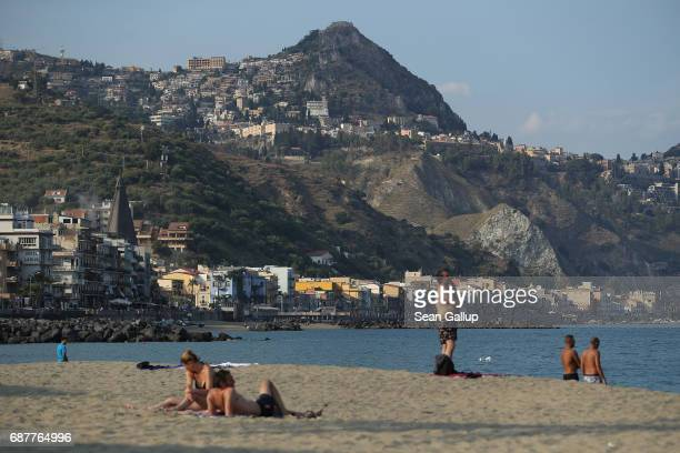People relax on a beach as the historic town of Taormina, which will host the upcoming G7 summit, stands perched on rocks behind on the island of...