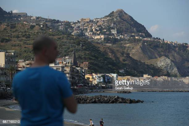 People relax on a beach as the historic town of Taormina which will host the upcoming G7 summit stands perched on rocks behind on the island of...