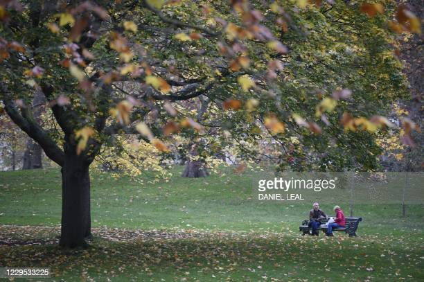 People relax on a bench in Green Park in central London on November 8, 2020 during a second national lockdown designed to contain soaring infections...