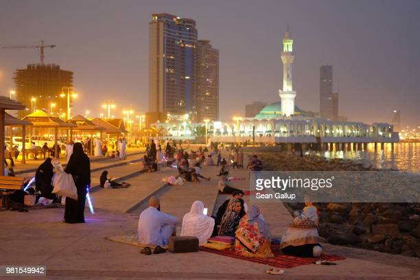 People relax on a Friday evening along the Corniche waterfront as the Al Rahma mosque stands behind on June 22 2018 in Jeddah Saudi Arabia The Saudi...