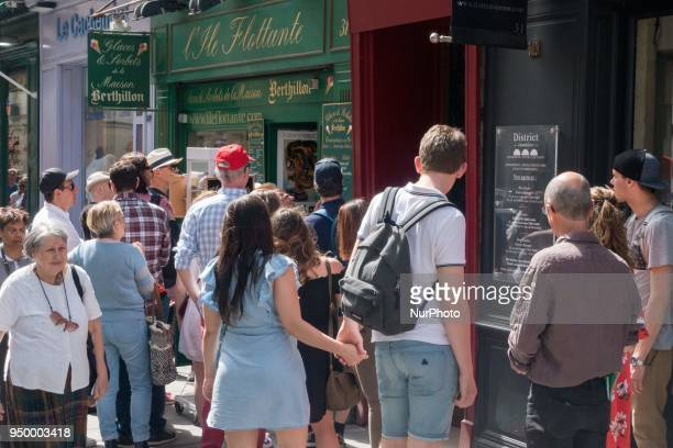 People relax on a warm weather Spring day and queue to buy a luxury Berthillon ice cream on April 22 2018 on the IleSaintLouis in Paris