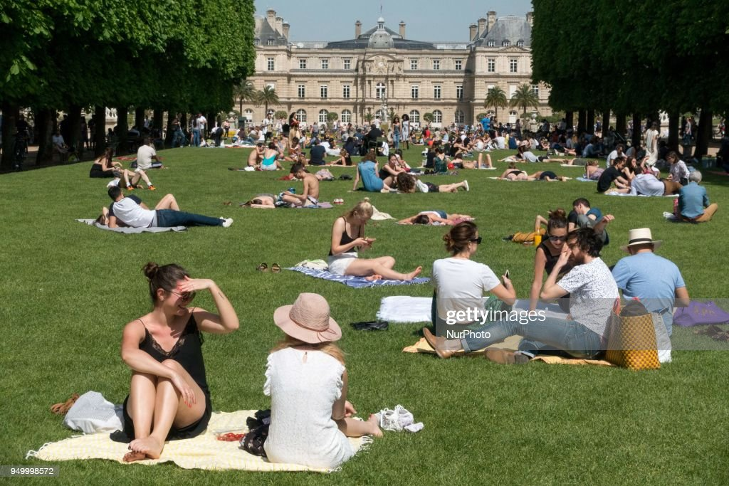 People enjoy the sun and warm spring temperatures in Paris