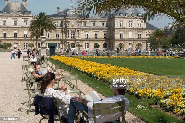 People relax on a warm weather Spring day in the Luxembourg garden in Paris on April 22 2018