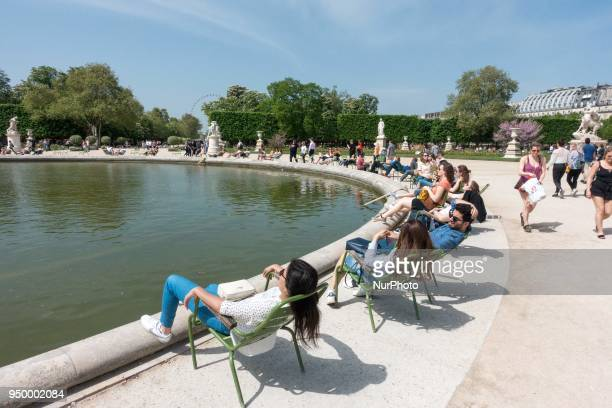 People relax on a warm weather Spring day in the Tuileries garden in Paris on April 22 2018