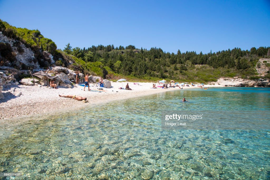 People relax on beach and swim in clear bay : Stock Photo