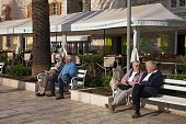 people relax benches along seafront promenade