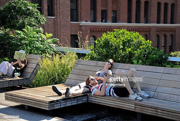 People relax on benches at the High Line park in New York US on Thursday Aug 16 2012 The High Line is a public park built on an elevated freight rail...