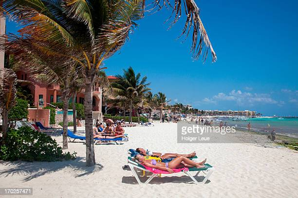 people relax on lounge chairs at beach - playa del carmen stock pictures, royalty-free photos & images