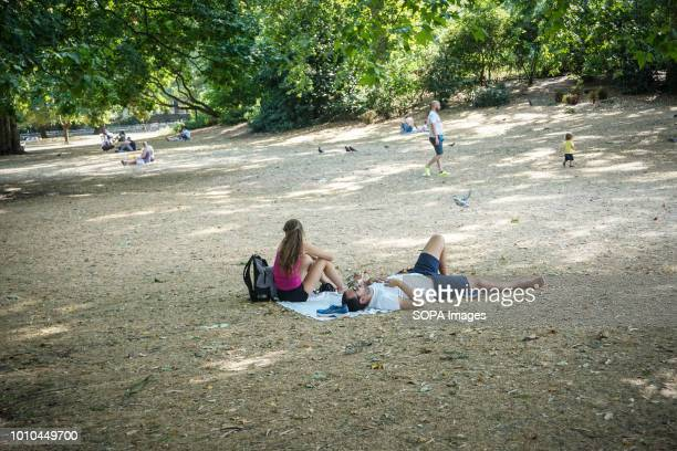 People relax on parched grass during a sunny day in St James Park Another heat wave is scheduled to hit parts of the UK this weekend