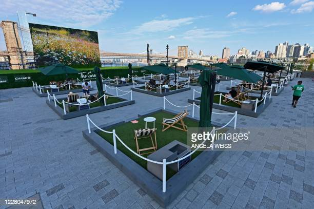 "People relax on socially distant mini lawns at the rooftop of Pier 17, called ""The Greens"", on August 14, 2020 in the Seaport District of New York..."