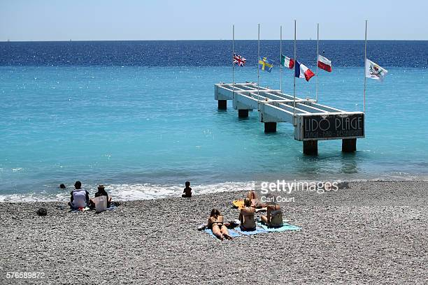 People relax on the beach as flags are flown at half mast on the Promenade des Anglais on July 16 2016 in Nice France Five people believed to be...