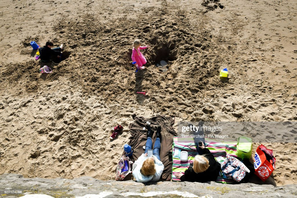 People relax on the beach during sunny weather at Barry Island in South Wales as temperatures remain in single figures.