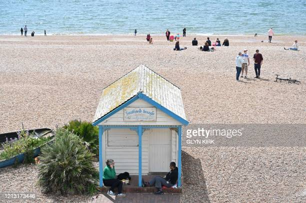 People relax on the beach in Brighton, southern England, on May 16 following an easing of lockdown rules in England during the novel coronavirus...