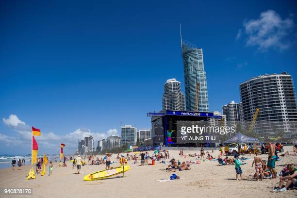 People relax on the beach near a stage set up for events ahead of the 2018 Gold Coast Commonwealth Games on the Gold Coast on April 2 2018 / AFP...